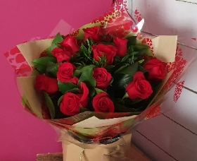 The Classic Dozen of red roses and foliage in a presentation bag
